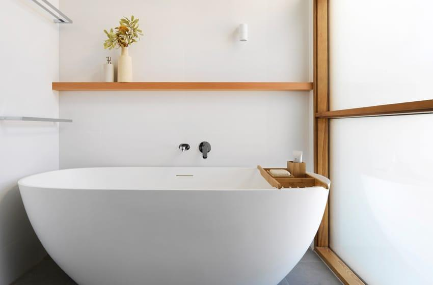 minimalist bathroom with white round bathtub and timber shelving
